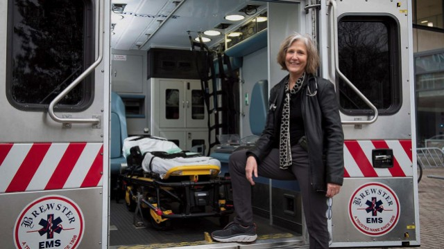 Pediatrician Eileen Costello stands next to the Boston Medical Center's mobile pediatric clinic.