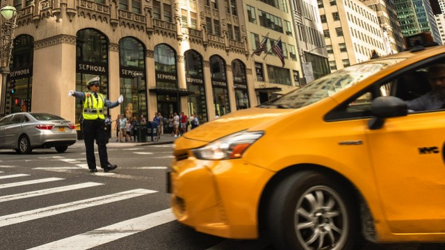 A yellow cab turns through an intersection directed by a police officer