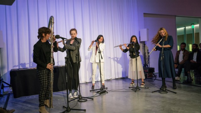 Five flutists playing together on stage