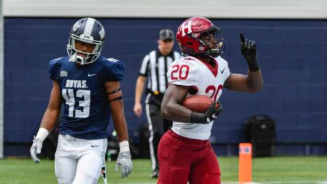 Harvard junior Aaron Shampklin (20) singed Georgetown defenders such as Jonathan Honore for 186 yards and two touchdowns.