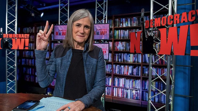 Amy Goodman featured in her broadcast studio giving the peace sign