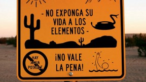 Near Winterhaven, California, an official sign faces south to warn illegal immigrants of dangers in the desert trek—heat, rugged terrain, rattlesnakes, lack of drinking water, a chance of drowning in a nearby canal—adding that it is not worth the risk.