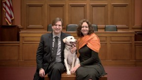 Chris Green and Kristen Stilt in Austin Hall's Ames courtroom with Lola, Stilt's rescue dog from Egypt