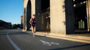 A man runs around the perimeter of Harvard Stadium