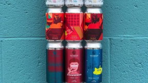 A colorful stack of beer cans against a blue wall