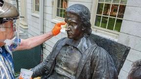 Conservators from Skylight Studios work on the John Harvard statue