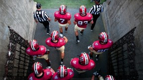 Photo of Harvard football players heading onto the field