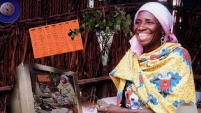 A grinning woman in traditional Nigerian dress sits cross-legged on the floor surrounded by modern devices, including a power strip, a land-line telephone, and a desktop computer displaying on its screen a duplicate image of the entire montage.