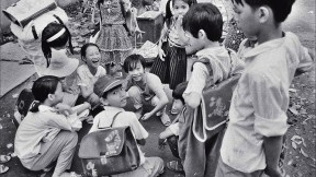 """Black and white photo of a group of Vietnamese children, titled """"Schoolchildren Playing Cards"""""""