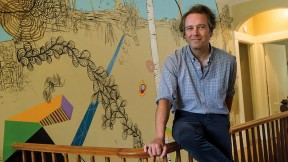 """Dan Chiasson at home in front of a """"sometimes delightful, sometimes disturbing"""" mural by David Teng Olsen, which appears in The Math Campers."""