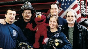 Four New York firefighters with John Weidman and <i>Sesame Street</i> character Elmo in 2001.