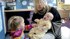 Mary Kinsella Scannell, vice president for early education and care, plays with baby Kinsey Ferraguto and toddler Margot Vorhees.