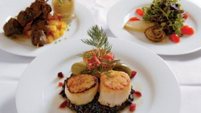 Scallops atop black sticky rice; behind, beef satay and baby greens