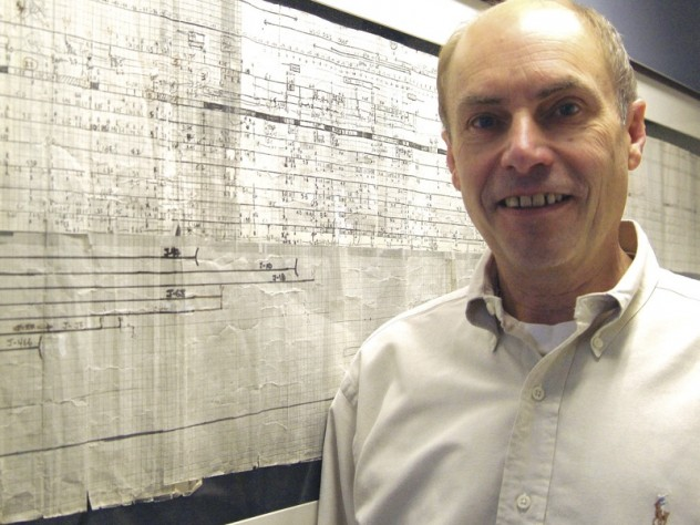 Kunkel with a six-foot-long map showing a portion of the area where the dystrophin gene is located within the human genome. This framed, hand-drawn original was started in 1983 and published in 1986, in the days before high-speed DNA sequencing.