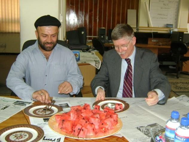 Farivar enjoys watermelon with a U.S. diplomat.