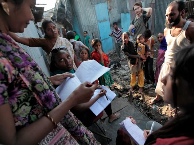 Azalea Ayuningtyas (bottom right) and Joyce Gitangu (sunglasses on head) interview a man about sanitation and water access as Lavina Fernandez (left) translates.