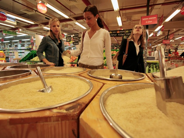 Kara Scarbrough, Alma Donohoe, and Edison examine the many varieties of rice for sale at this hypermarket.