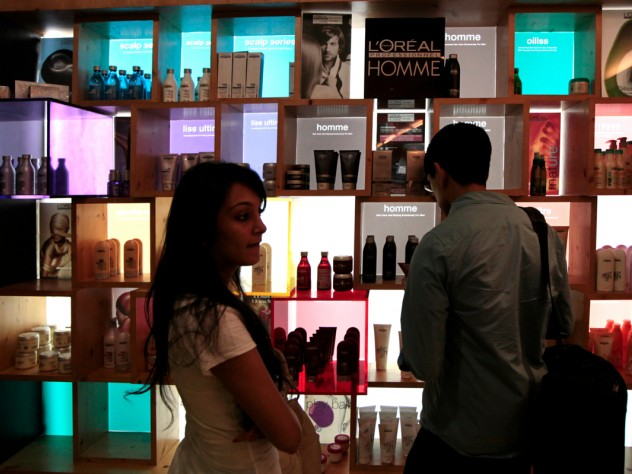 """Another group advised a company on introducing a new line of hair-care products. Here, M.B.A. student Nafis Atiqullah (right) examines a product display at a hair salon. At left is Riddhi Paleja; her aunt, the Harvard students' local guide, brought her along for the day because she thought the students might find it informative to interview her. She is, her aunt said, """"the only person I know who uses a lot of hair products."""""""