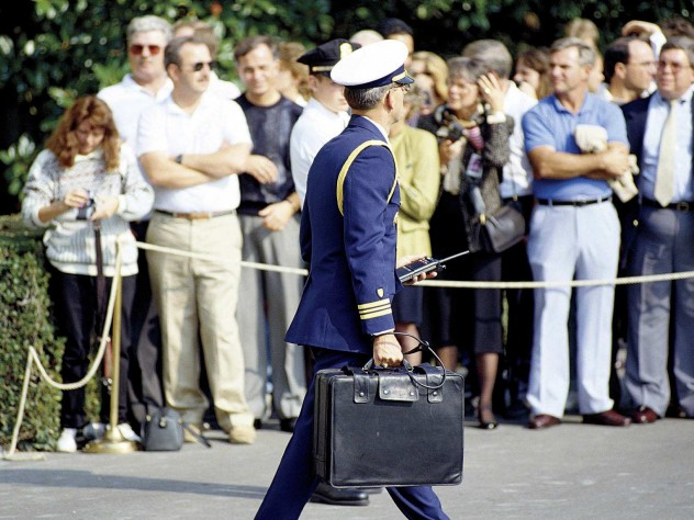 """A military aide to President George H.W. Bush carries the """"nuclear briefcase,"""" cabled to his wrist, in 1991."""