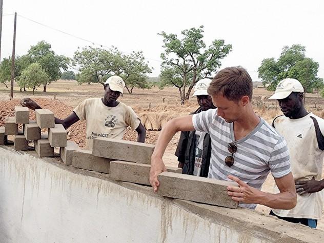 Jordan MacTavish, M.Arch. '12, demonstrates how the Sinthian Cultural Center's patterned brickwork will allow for ventilation.