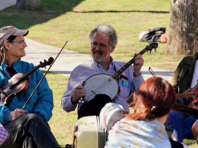 Two fiddlers and a banjo player take a break during an outdoor performance.