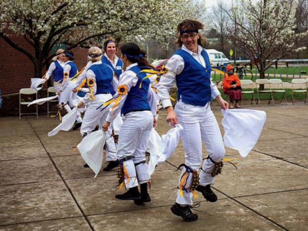 Morris dancers in white trousers and colorful vests wave handkerchiefs as they dance.