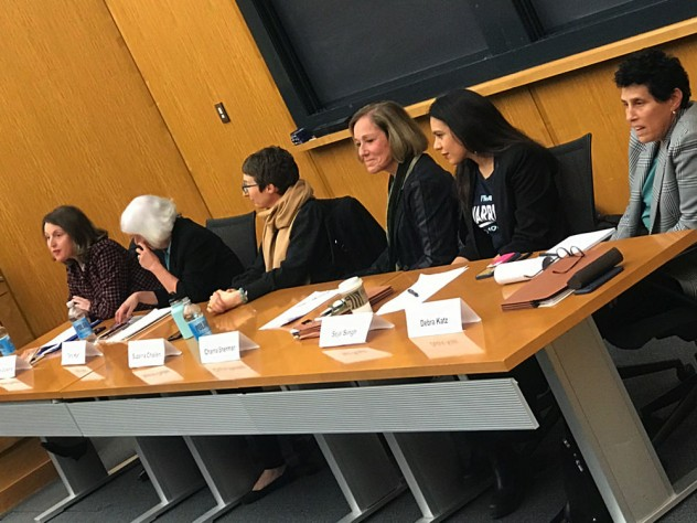 Six women sit at a table at the front of an auditorium.