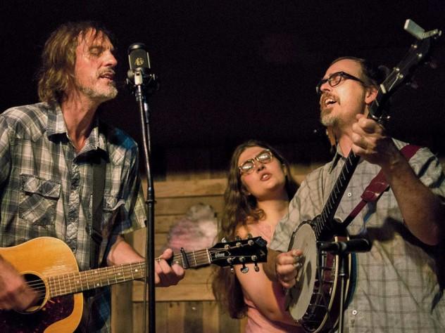A bluegrass guitarist, banjoist, and singer perform on stage