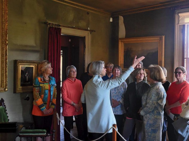 A tour party views works to art at The Evergreens