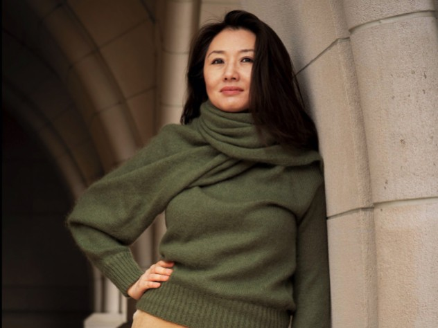 Portrait of Jeannie Suk Gersen, an elegantly dressed Korean American woman leaning against a stone archway.