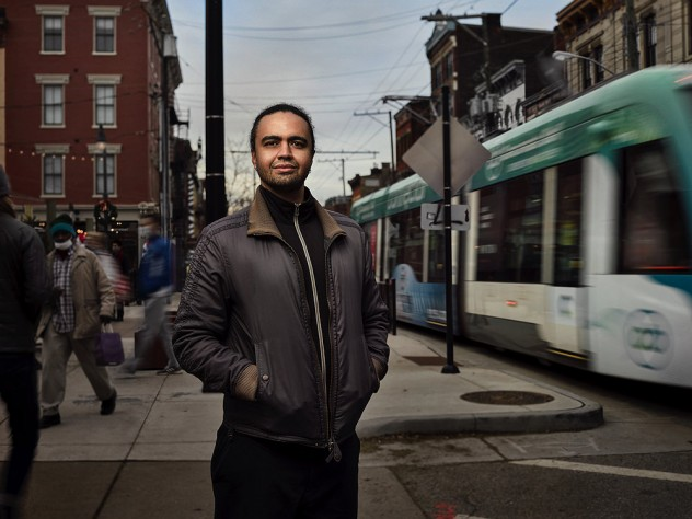 Stephen Gray stands on city sidewalk with street car passing by on right