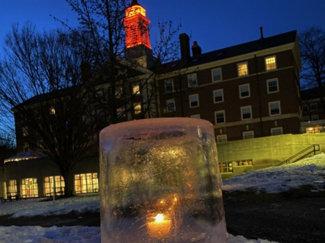 """Close-up image of an """"ice lantern"""" (a light set in an ice casing) in the snow on Radcliffe Quad"""