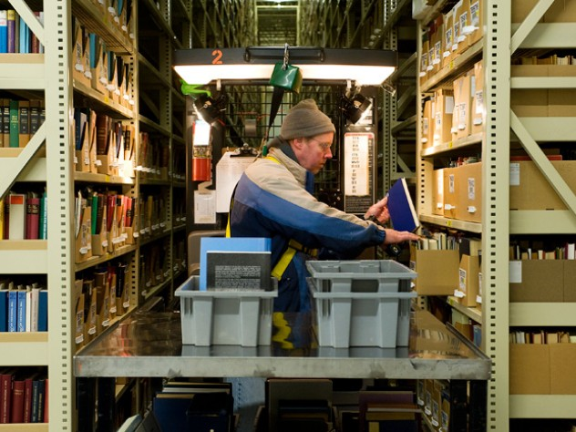 Nearly half of Harvard's collection is housed at the Harvard Depository, a marvel of efficient off-campus storage. Library assistant Carl Wood reshelves books in the 30-foot-high, 200-foot-long stacks.
