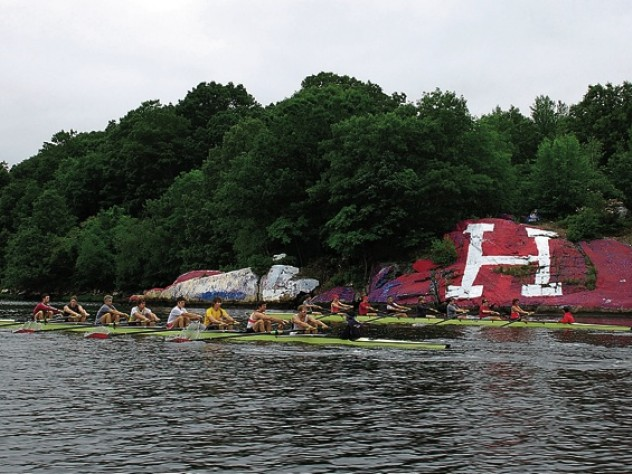 """Two Harvard crews (right) row past """"The rock,"""" long contested as a site for Harvard or Yale partisan artwork."""