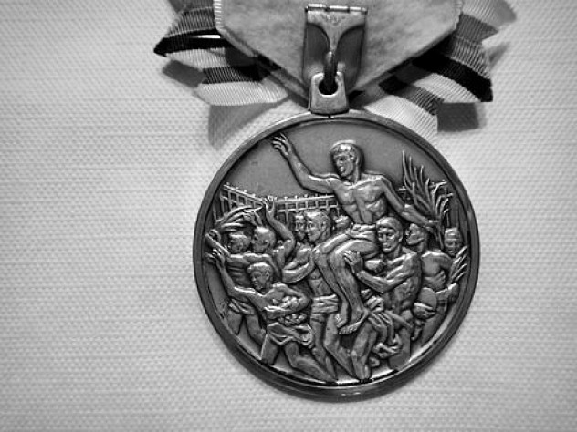 The silver medal he won and has now donated to the College swim team