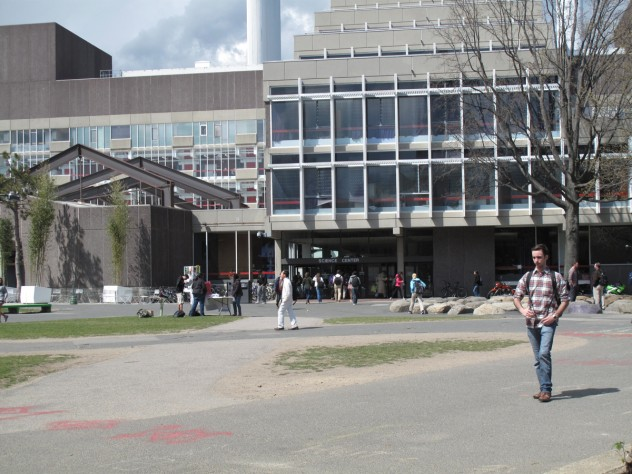 6. Preconstruction: the main pedestrian crossroads, seen from Harvard Yard looking north toward the main mass of the Science Center; the bamboo planters then in place, to the left, will be replaced with a much larger, continuous, permanent planting of mixed species, to form a shaded grove.