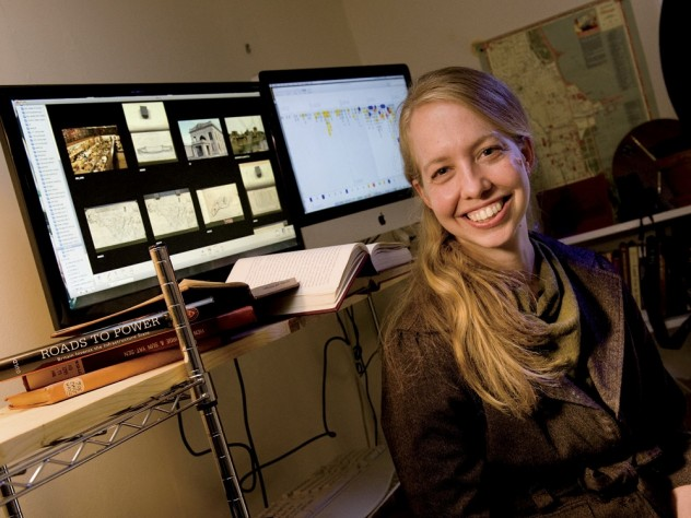 Historian Jo Guldi in her office at the Society of Fellows. She uses visualizations such as those shown behind her to aid her research.