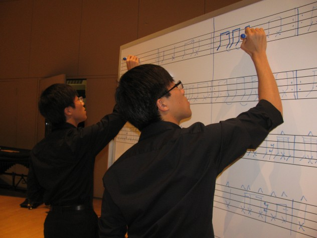 At a rehearsal, twins Seungsoo Kim '13 and Seungjun Kim '13 practice a number that involves tapping out sounds with markers on a whiteboard.