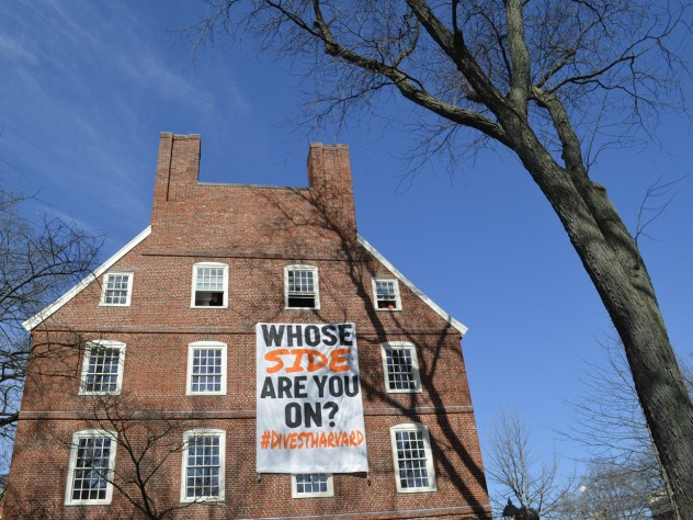 A Divest Harvard sign hangs from the windows of Mass. Hall.