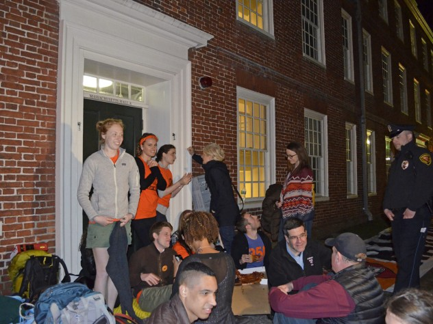 Students sit in front of an entryway to Mass. Hall, as Harvard University police look on.