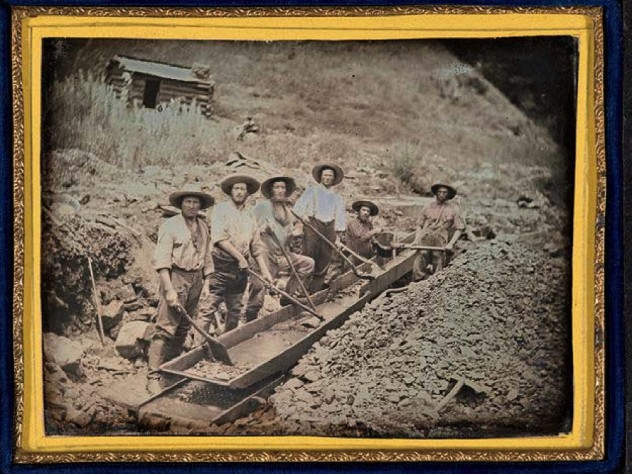 Gold miners working with a piece of gold-mining equipment called a long tom, circa 1850