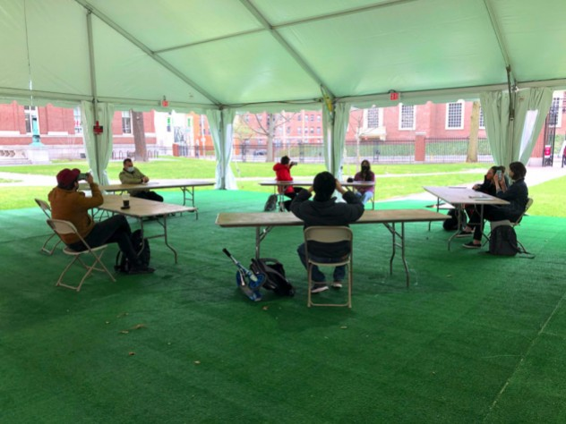 Students gather in desks under a tent, a pilot of outdoor instruction for performance-based courses