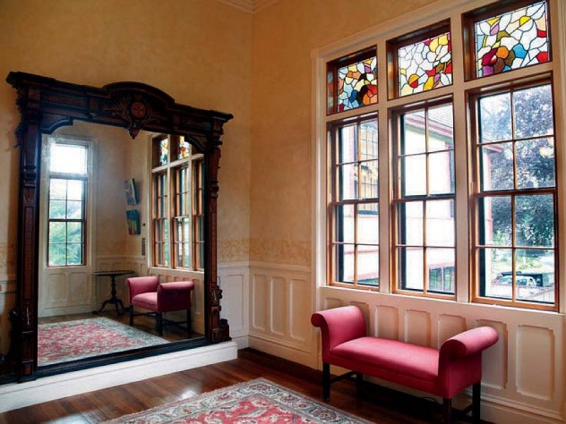 Highfield Hall's large wall mirror, stained glass, and other architectural details