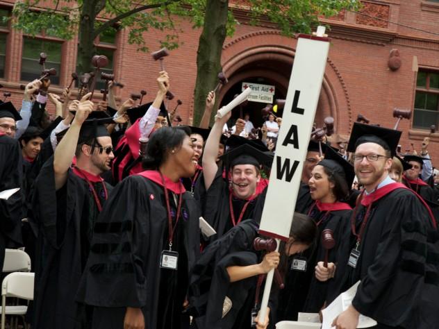Harvard Law School graduates celebrate, gavels in hand.
