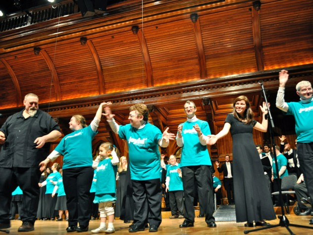 """Local composer Nick Page (at left), conductor of the Mystic Chorale, takes a bow with chorus and Collegium Musicum members after they performed his song """"Do You Shine"""" (written especially for Joyful Noise) as an encore. Sharing the applause is Katie Fromm, daughter of the chorus's co-founder and conductor, Allison Fromm."""