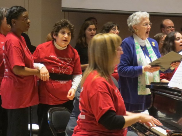 Composer, conductor, and arranger Alice Parker joins Joyful Noise and Collegium members in song. At the piano is the associate director of Joyful Noise, Cathy Sonnenberg; the group's co-founder, Beth Fromm, stands second from left.