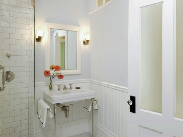 In an interior bathroom, transom windows and frosted glass allow natural light from an exterior window in the next room to reach the space. Allen chose to use period details such as wainscoting and molding to draw attention away from modern anachronisms like the frameless glass shower door.