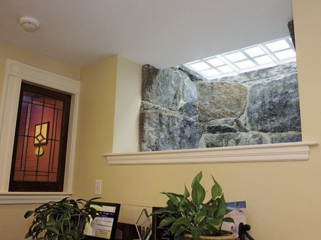 A granite-lined window well at the headquarters of Charlie Allen Restorations Inc. uses frosted glass pavers in the sidewalk to brighten a basement hallway.