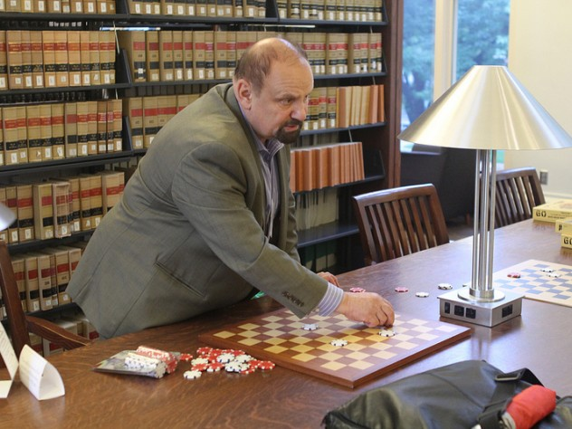 International draughts master Alex Mogilyansky with board and checkers in Langdell Library
