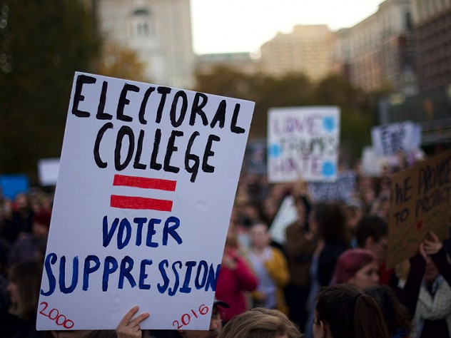 """A protester holding a sign that reads """"ELECTORAL COLLEGE = VOTER SUPPRESSION"""" on November 13, 2016."""
